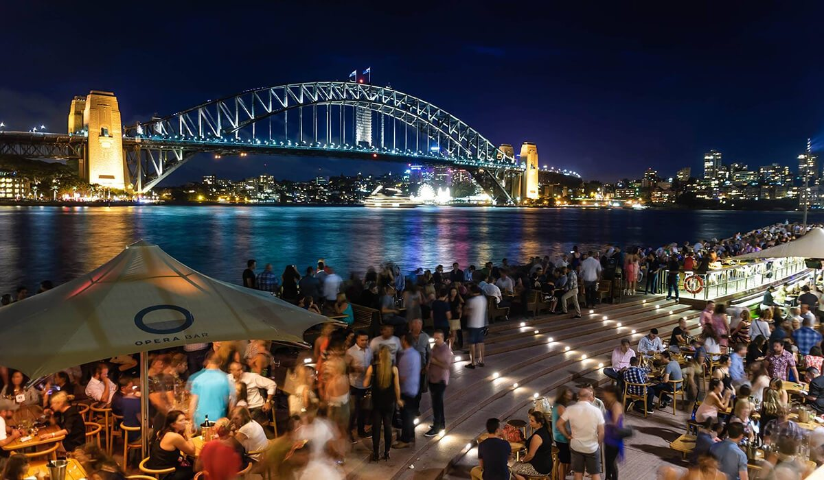 Sydney, Australia night city with bridge and lights in background, crowds of people