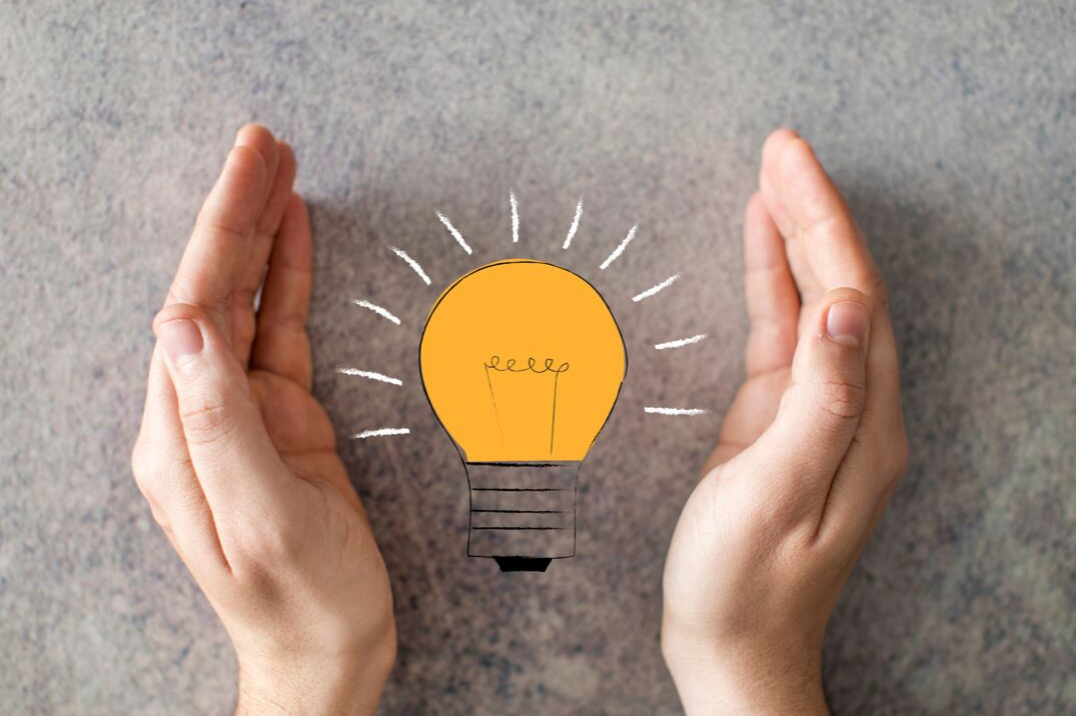 hands yellow light bulb gray background