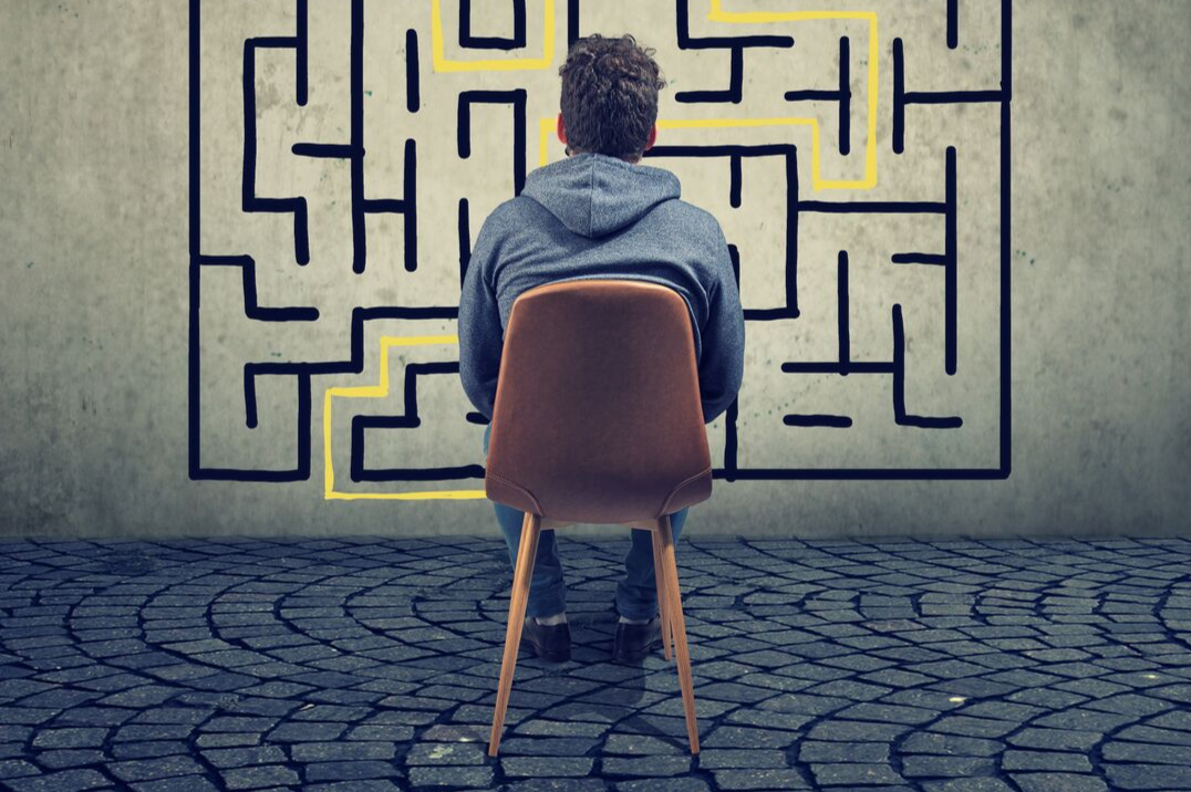 man sitting on a chair labyrinth wall
