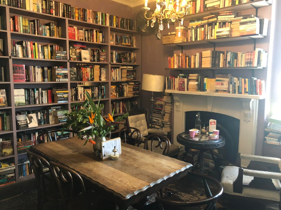 Image of a bookstore with a table and books on the walls