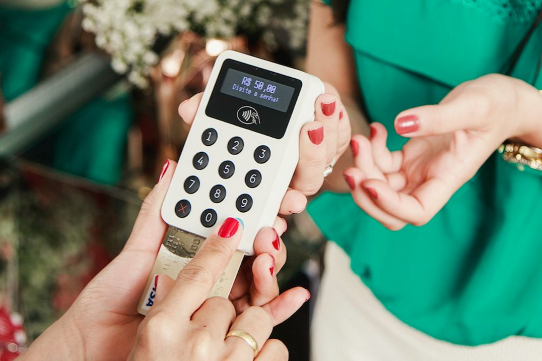 woman green blouse red nails izettle card reader