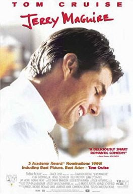 Tom Cruise looking down and smiling wearing a white shirt with his background out of focus red black and gold lettering overlaid