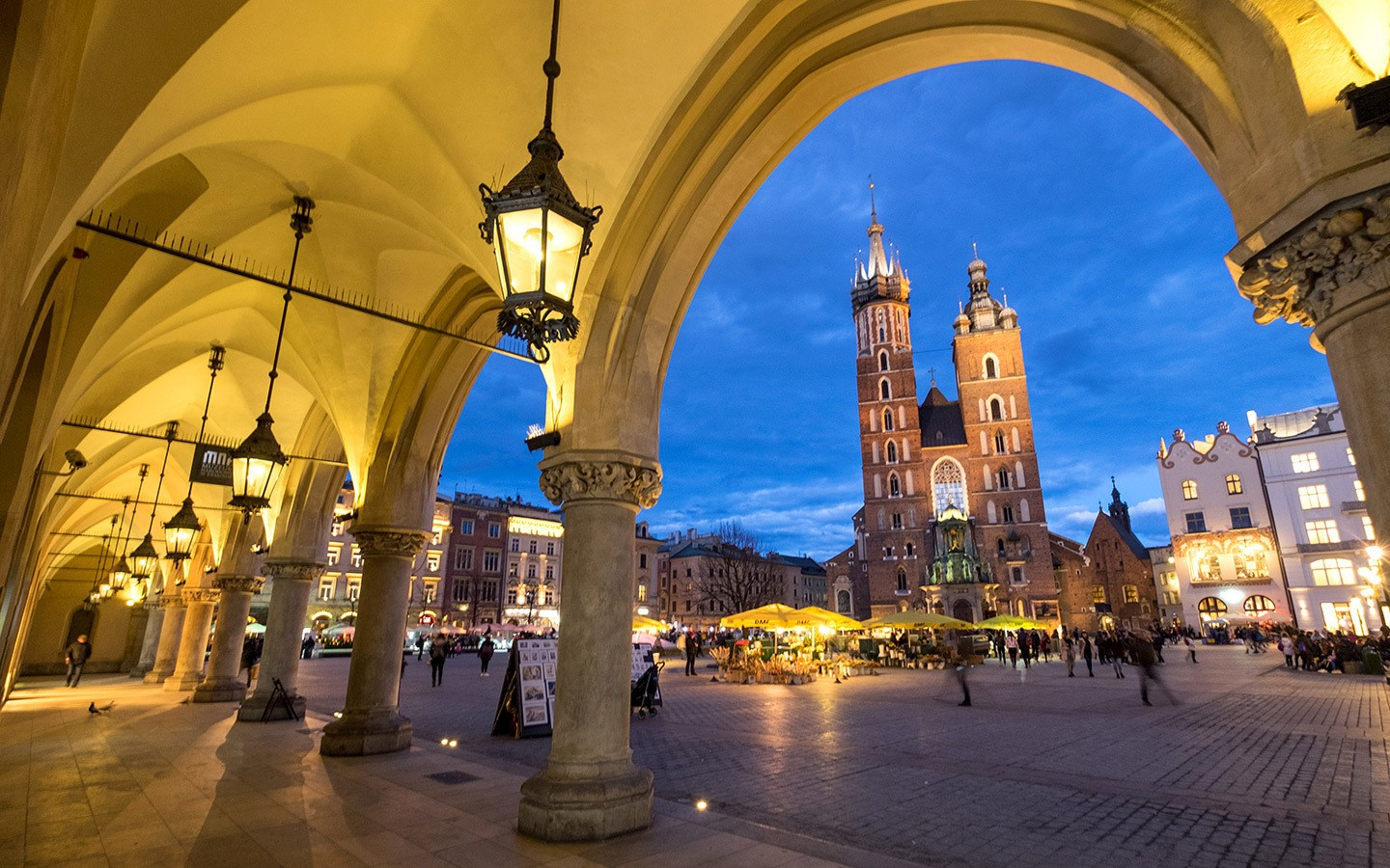 Krakow Poland at night with old church in square lamps and arches and a night market