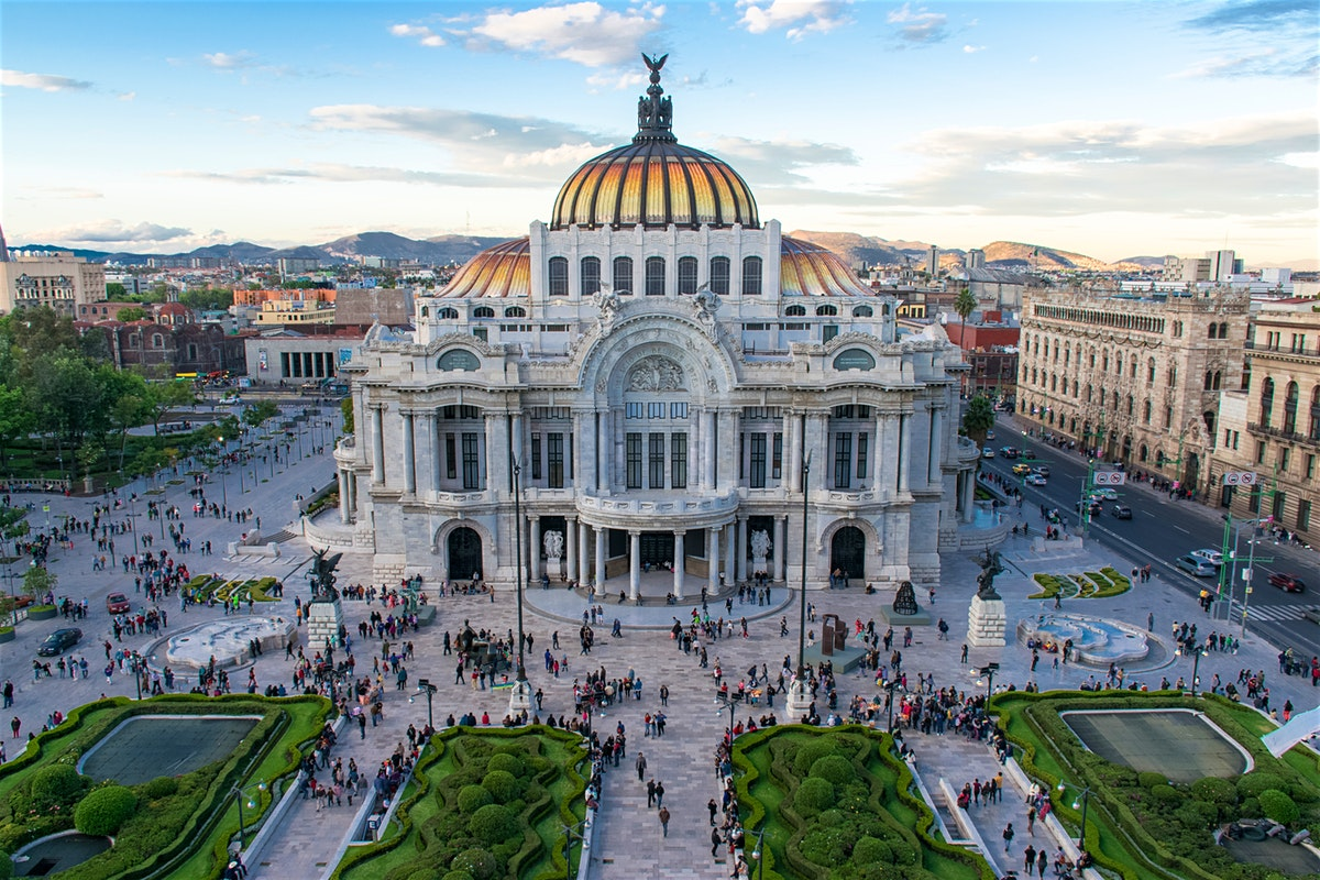 mexico city mexico with the palacio de bellas artes gardens and many people under a blue sky