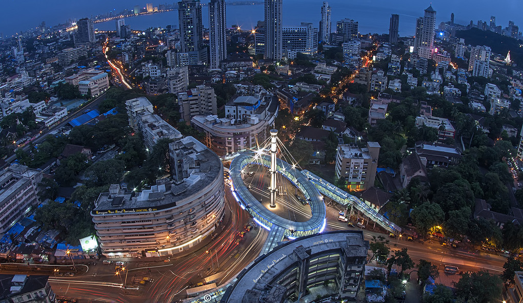 view of Mumbai India at night featuring many building green trees and the sea in the background