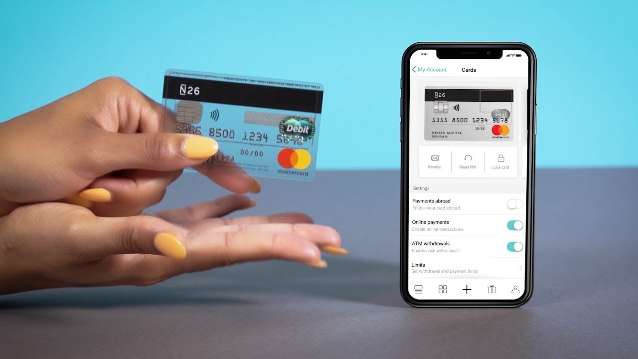 N26 bank card held in the hand of a woman who is comparing it to a mobile phone