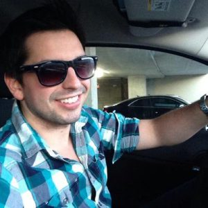twitter influencer paul hanus in sunglasses and blue shirt driving