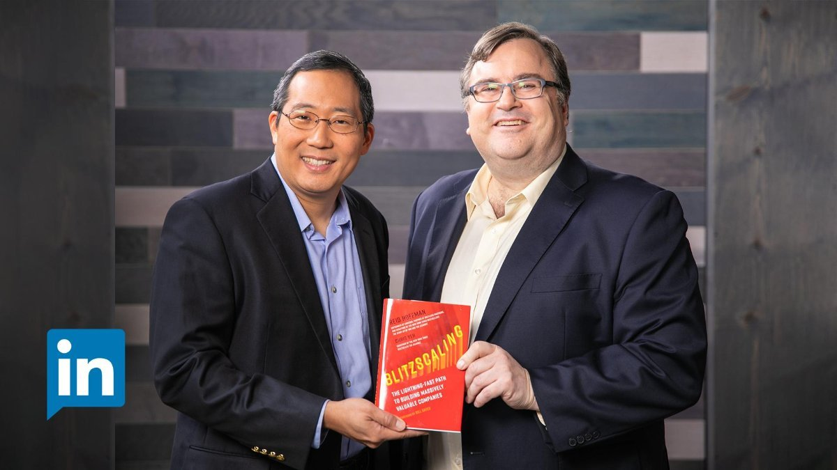 "Photo of Reid Hoffmann and Chris Yeh holding the book ""blitzscaling"""