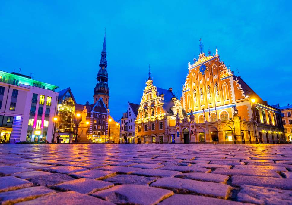 riga latvia church and town hall town square lit with purple and orange light