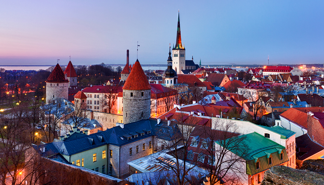 tallinn estonia white buildings red roofs sunset purple blue sky baltic sea trees