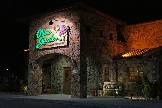 exterior of a stone-walled restaurant with a green and purple neon sign above the door at night