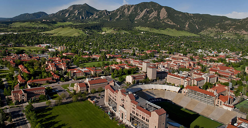 University of Colorado campus in Boulder featuring Boulder stadium university buildings student accommodation with a backdrop of green mountains and blue sky