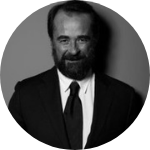 black and white photo, man standing by the wall, smiling, beard, white shirt, black suit, brown hair, black tie