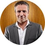 photo, man standing, smiling, white shirt, grey suite, ggrey hair, wooden background