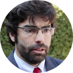 man, talking, white shirt, red tie, dark black suit, curly brown hair, glasses, beard