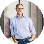 man, grey hair, wearing glasses, light blue shirt, jeans, he has hands in his pockets, standing next to the wall