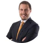 man smiling, white shirt, orange tie, black suit, short brown hair, moustache