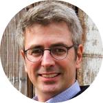 man smiling, grey hair, light blue shirt, black suite, glasses