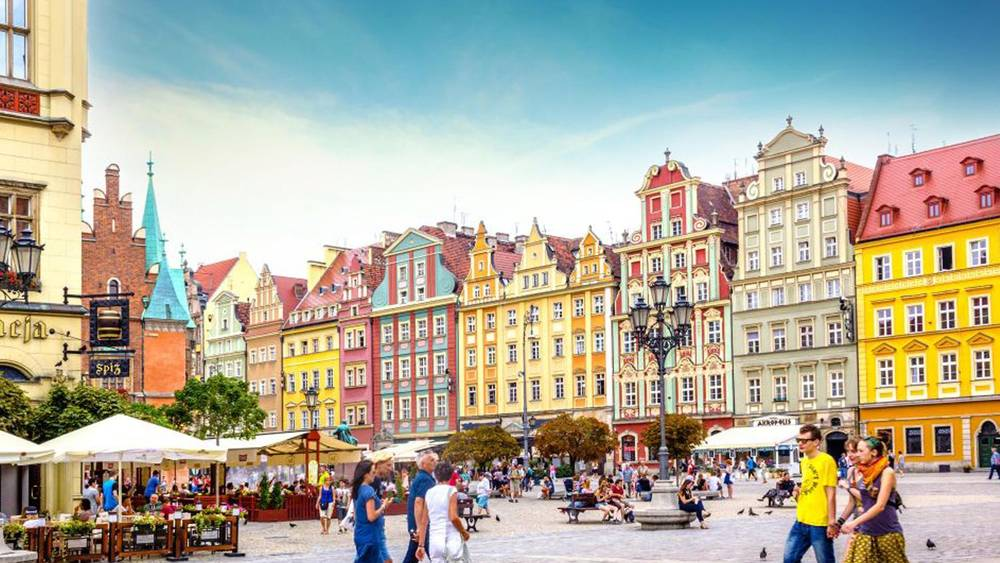 wroclaw poland colouful buildings town square tourist people church sky cafes restaurants