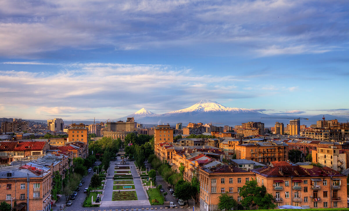 yerevan armenia green park orange buildings blue sky white clouds mountain with snow