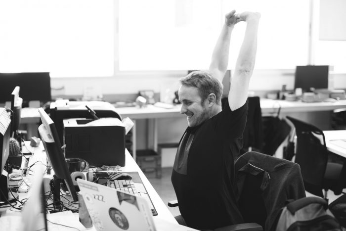 man at office stretching at desk, black and white