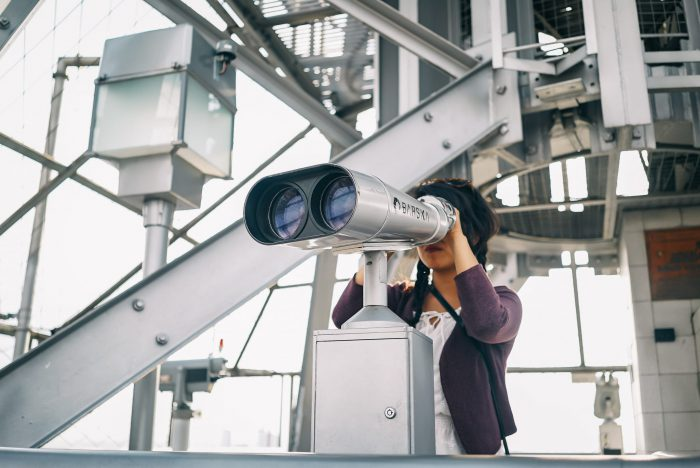 woman looking through public telescope on metal structure building