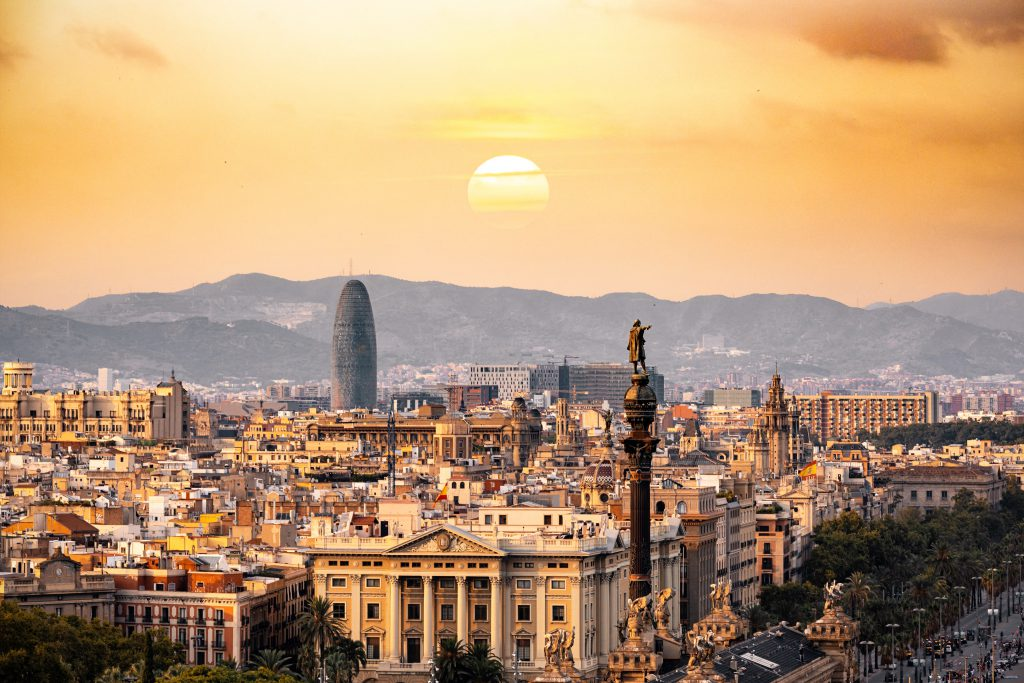 Barcelona, Spain city with mountains and sun in background