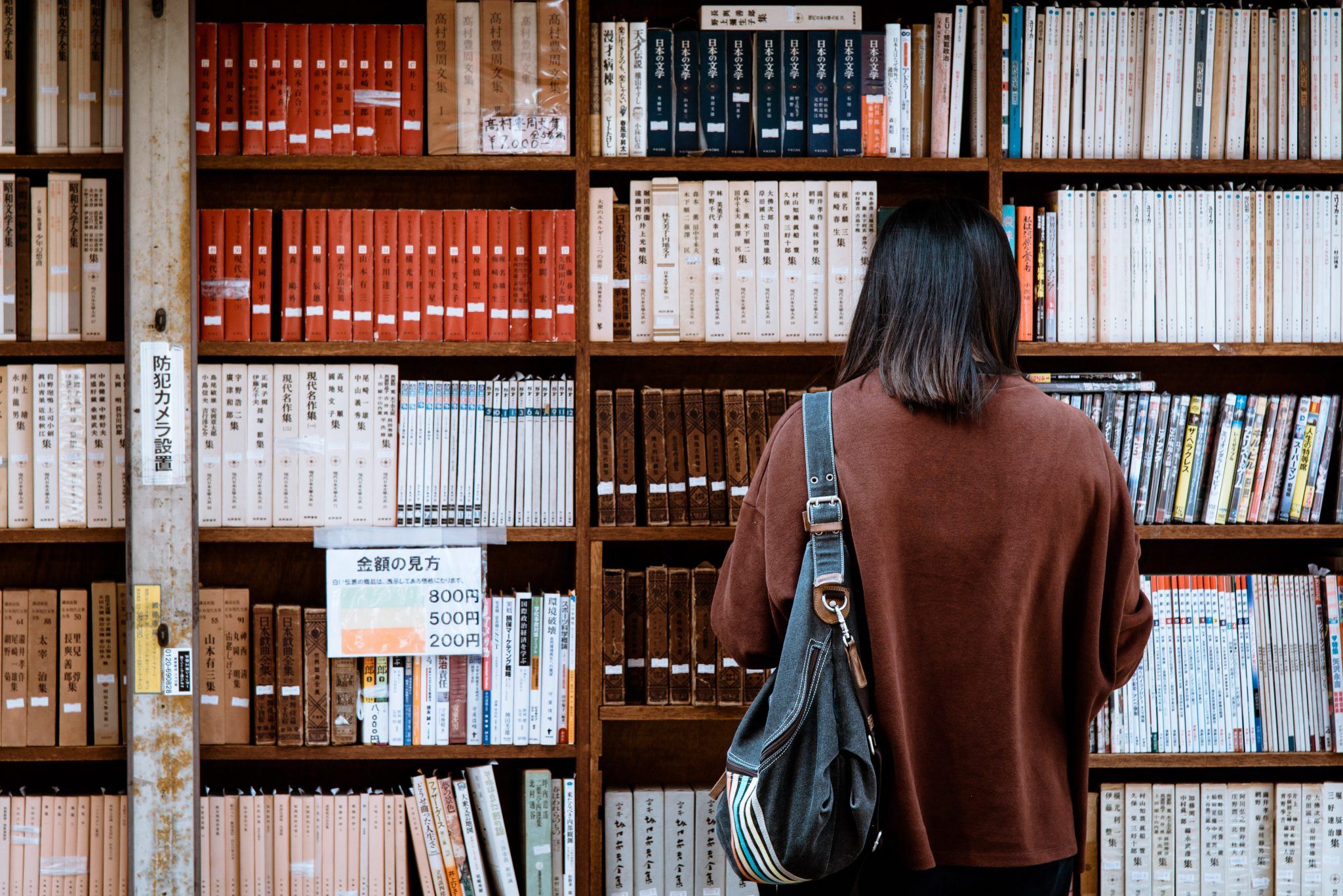 Person facing bookshelf with Japanese books