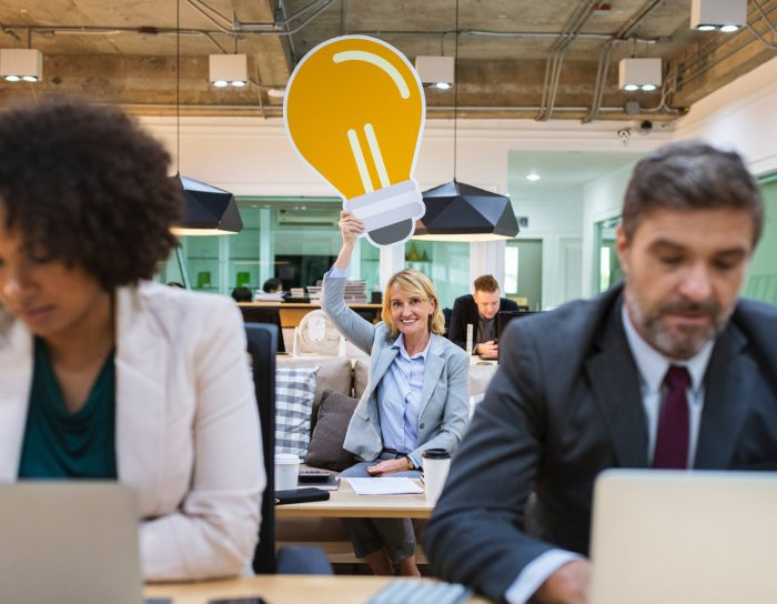 woman holding lightbulb icon above head in office