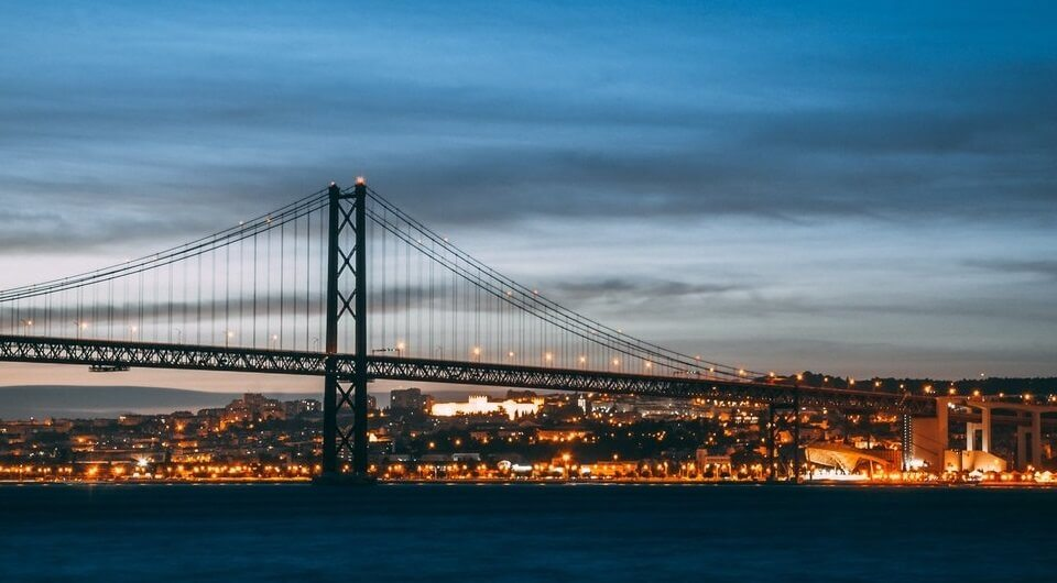Lisbon, Portugal city at night with lights and bridge