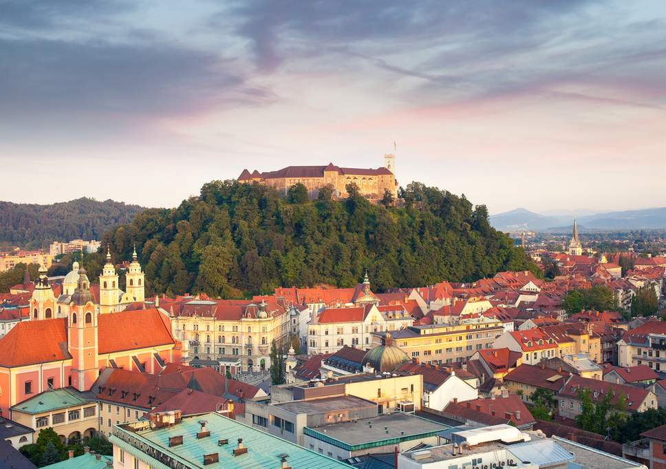 ljubljana slovenia old buildings orange roofs castle on the hill with green trees mountains sky clouds
