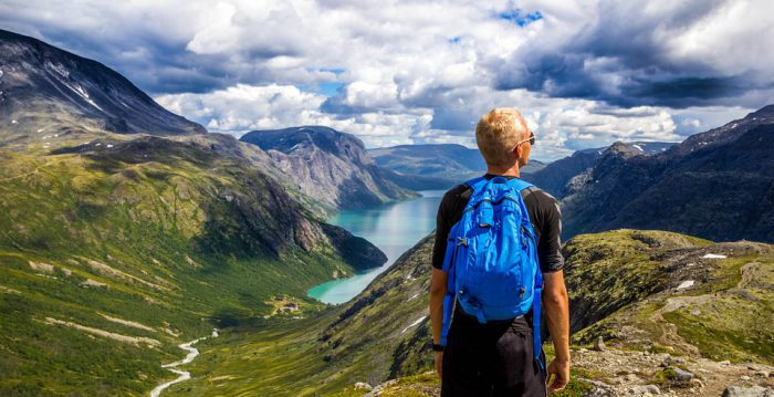person with blue backpack looking at mountains