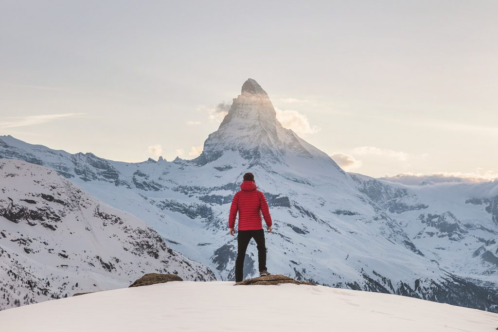 Man stands on a top of a mountain in snow
