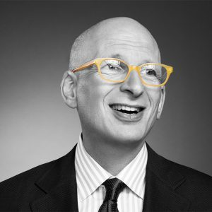 Black and white picture of Seth Godin with suit and yellow glasses
