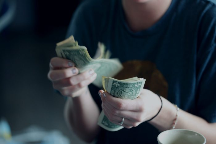 Investment, girl counts money with hands