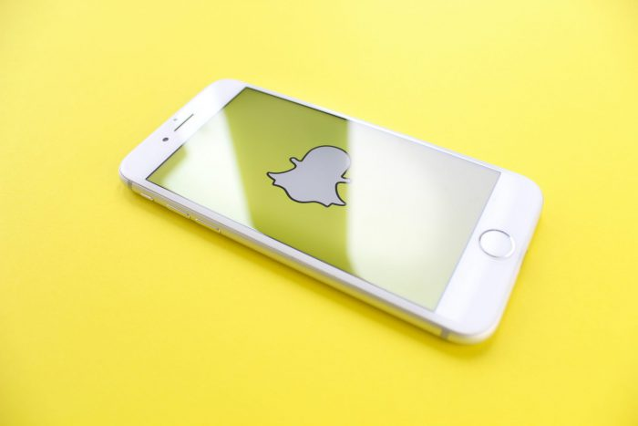 an white iphone displaying the snapchat logo on a yellow background