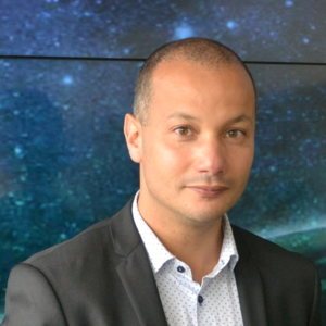 Nabil Bouzerna in a black suit and white shirt with a galaxy background