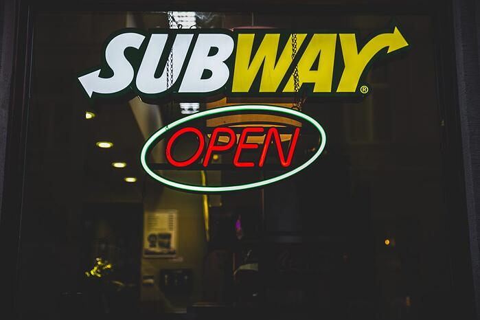 subway neon sign in white yellow and ted