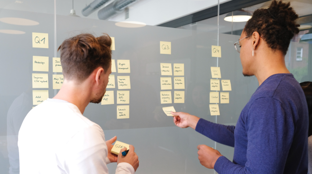 A man and a woman putting post-it notes on a board